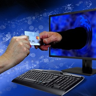 a hand reaches out of a computer monitor to grab a credit card from another hand